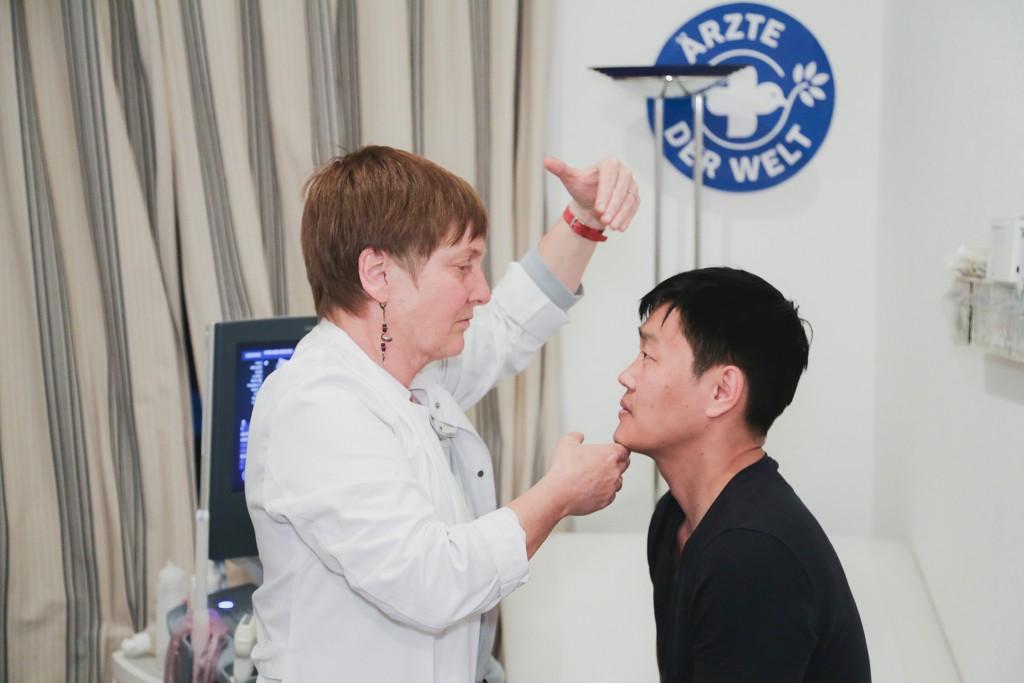 Eine Ärztin untersucht einen Patienten